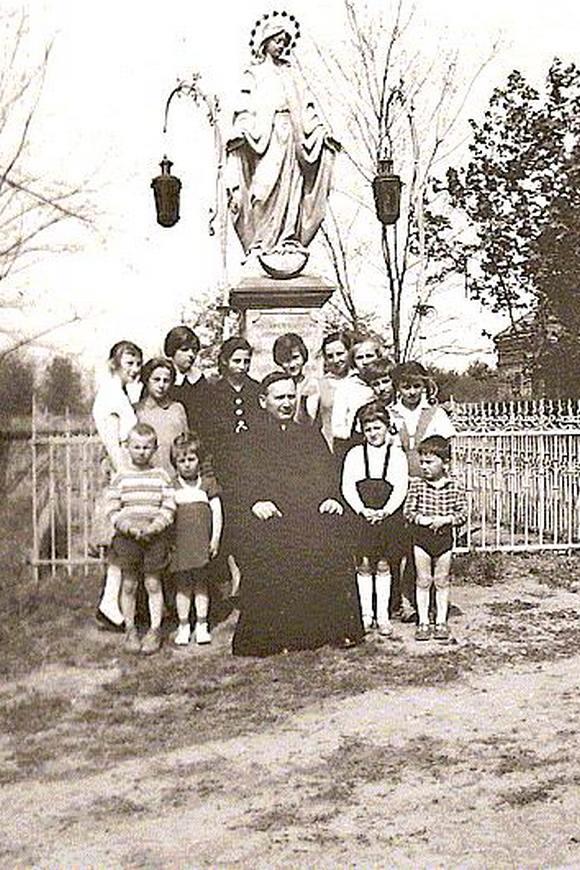 Proboszcz w asyście dzieci pod figurą Niepokalanej ok. 1956 r.